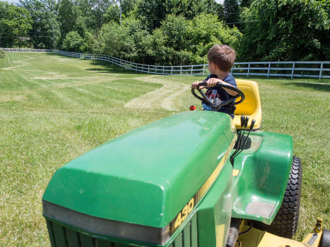 Boy checks out his lawnmower driving skills